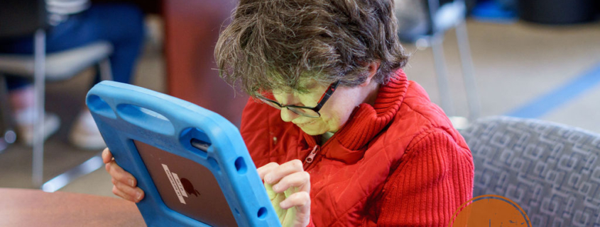 Developmentally disabled woman works on tablet